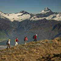 Trekkers on Buchanan peak with Mount Aspiring behind, walking above Matukituki valley, near Lake Wanaka | Colin Monteath
